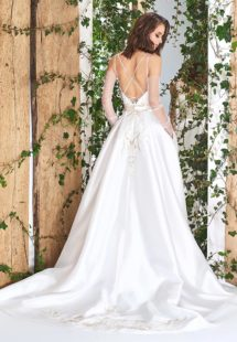 Style #1821L, lace embroidered a-line wedding gown with deep plunging neckline features crisscross spaghetti straps over the low back and satin skirt with pockets, available in ivory
