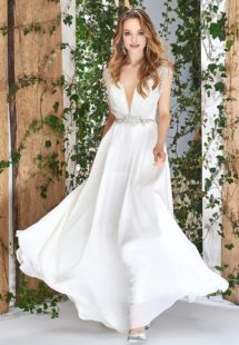 Style #1823L, sleeveless sheath wedding gown with deep plunging neckline features beaded strings over the top, embellished belt, and chiffon skirt, available in ivory