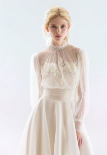 Style #18/1900L, bishop sleeve wedding dress with high neckline and lace embroidery on the bodice, button-up illusion back, and flowy organza skirt, available in ivory