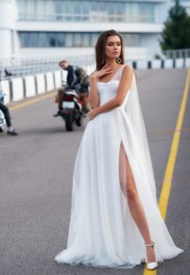 Style #12064, bridal gown with pearl embellishments and cape sleeves, available in ivory