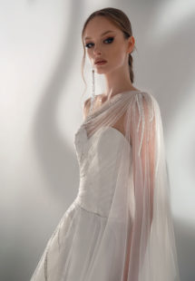 Style #2101, A-line wedding dress with one-shoulder cape sleeve, available in ivory