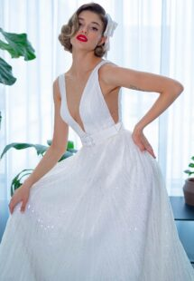 Style #2205L, sequinned lace A-line wedding dress with plunging V-neckline and belt, available in ivory
