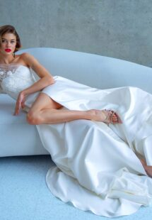 Style #2215L, one-sleeve ball gown wedding dress with high slit and pockets, available in ivory